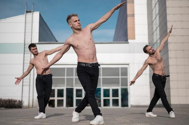 Vooraanzicht van shirtless hiphopdansers die buiten repeteren Gratis Foto