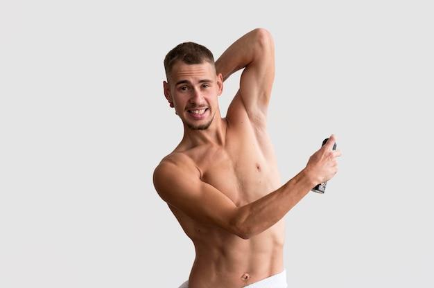 Vooraanzicht van shirtless man deodorant toe te passen Premium Foto