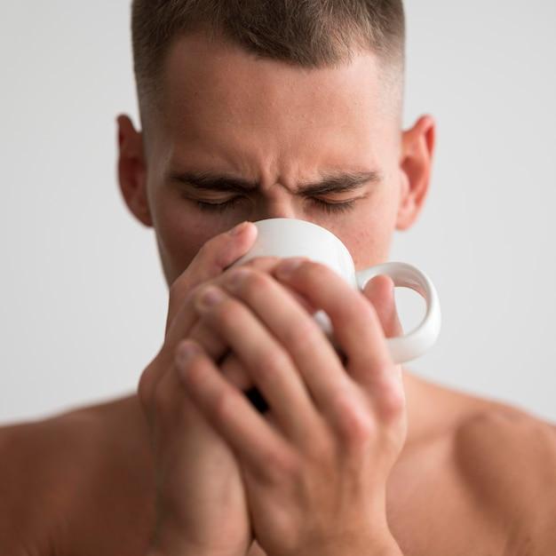 Vooraanzicht van shirtless man koffie drinken in de ochtend Gratis Foto