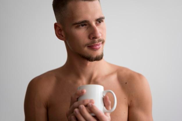 Vooraanzicht van shirtless man met koffiemok in de ochtend Gratis Foto