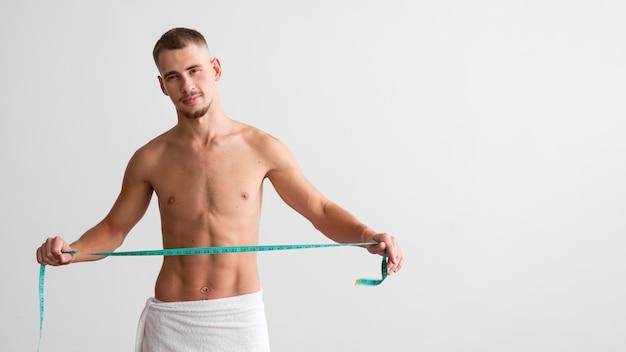 Vooraanzicht van shirtless man met meetlint met kopie ruimte Gratis Foto