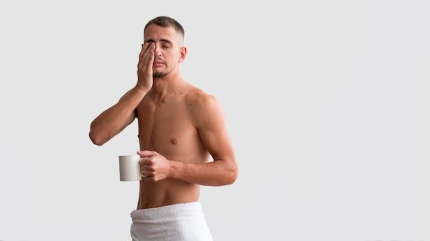 Vooraanzicht van shirtless slaperige man in de ochtend met koffie Gratis Foto
