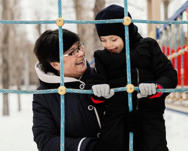 Vooraanzicht van smiley grootmoeder en kleinzoon buiten in de winter in het park Gratis Foto