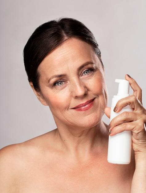 Vooraanzicht van smiley oudere vrouw met fles reinigingsmiddel voor huidverzorging Gratis Foto
