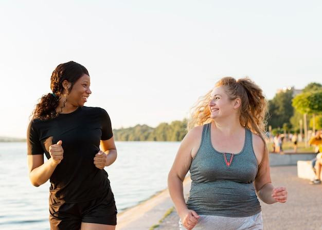 Vooraanzicht van smiley vriendinnen samen joggen Premium Foto