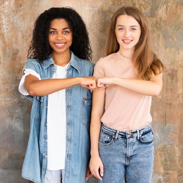 Vooraanzicht van smiley vriendinnen vuist stoten Gratis Foto