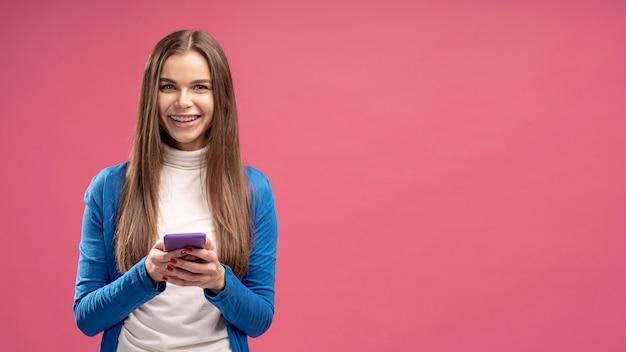 Vooraanzicht van smiley vrouw met smartphone Gratis Foto
