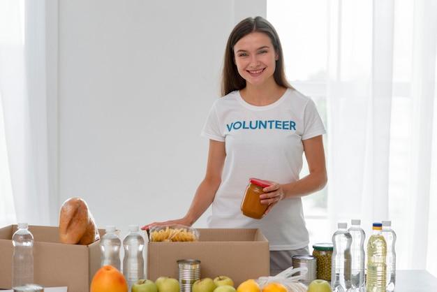 Vooraanzicht van smiley vrouwelijke vrijwilliger die met voedselschenkingen helpt Gratis Foto