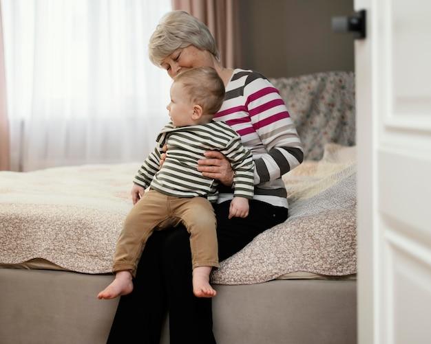 Vooraanzicht van smileygrootmoeder die haar kleinzoon houdt Gratis Foto