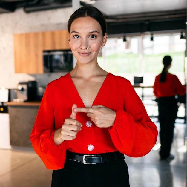 Vooraanzicht van smileyonderneemster die gebarentaal gebruikt Gratis Foto