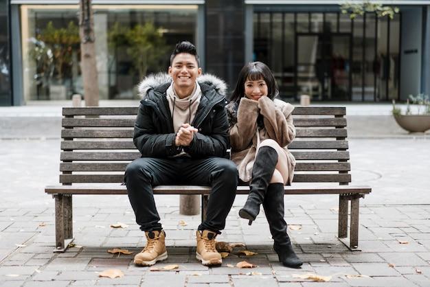 Vooraanzicht van smileypaar zittend op een bankje Premium Foto