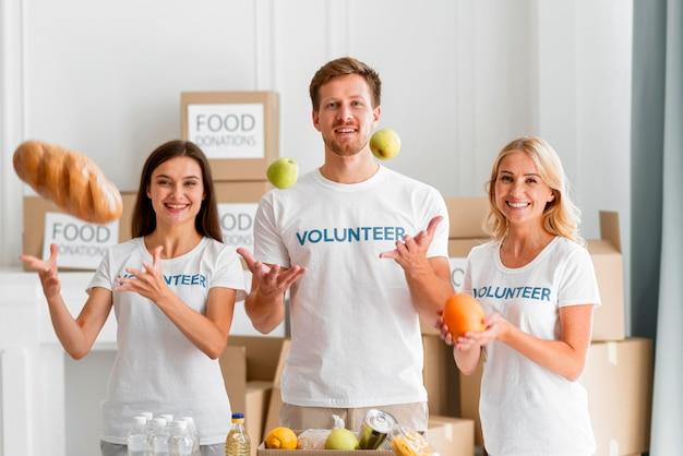 Vooraanzicht van smileyvrijwilligers die met voedseldonaties helpen Gratis Foto