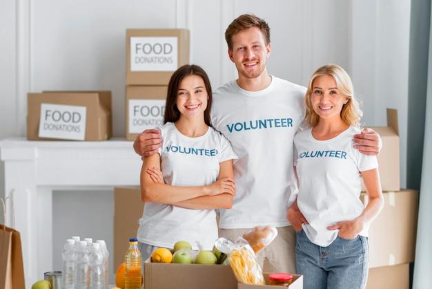 Vooraanzicht van smileyvrijwilligers poseren met voedseldonaties Gratis Foto