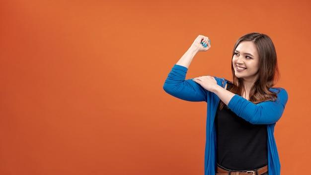 Vooraanzicht van smileyvrouw die haar biceps toont Gratis Foto