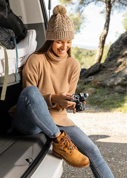 Vooraanzicht van smileyvrouw die in de kofferbak van de auto zit terwijl op een roadtrip en camera vasthoudt Premium Foto