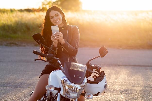 Vooraanzicht van smileyvrouw die smartphone bekijkt terwijl zij op haar motorfiets zit Gratis Foto