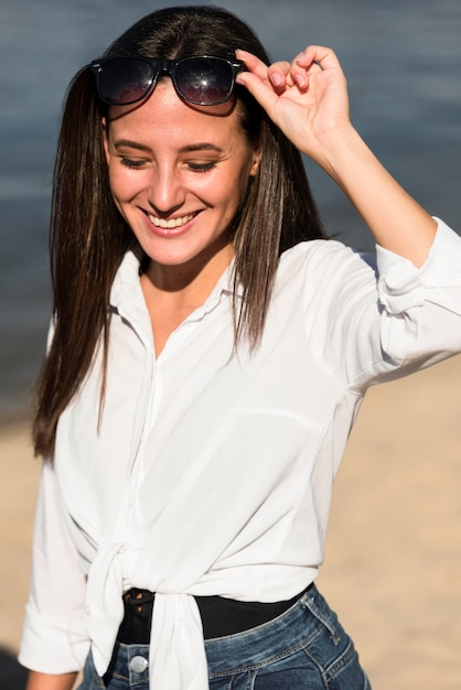 Vooraanzicht van smileyvrouw met zonnebril op het strand Gratis Foto