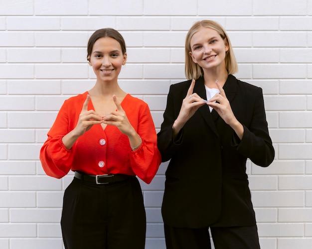 Vooraanzicht van smileyvrouwen die gebarentaal gebruiken Gratis Foto