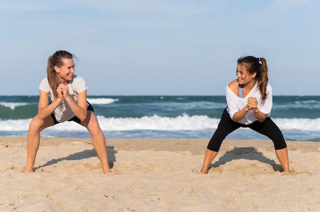 Vooraanzicht van twee vrouwen die op het strand uitoefenen Gratis Foto