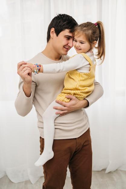 Vooraanzicht van vader die zijn dochter houdt Gratis Foto