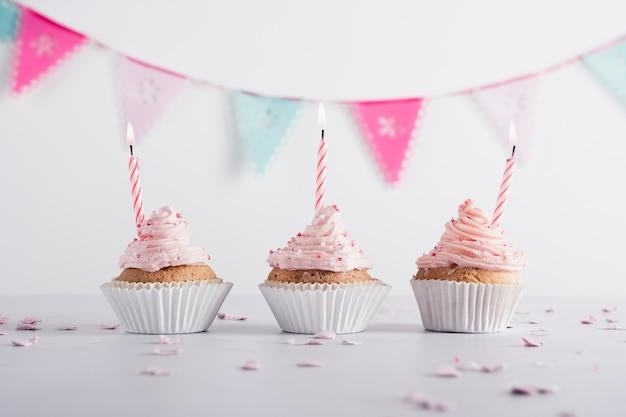 Vooraanzicht van verjaardag cupcakes met aangestoken kaarsen en slinger Gratis Foto