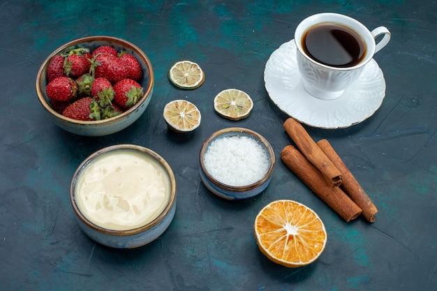 Vooraanzicht van verse rode aardbeien met kaneel en kopje thee op blauw bureau Gratis Foto