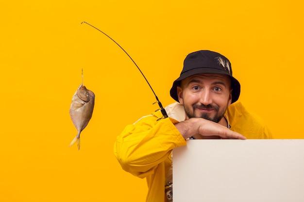 Vooraanzicht van visser die terwijl het houden van hengel met vangst stellen Gratis Foto