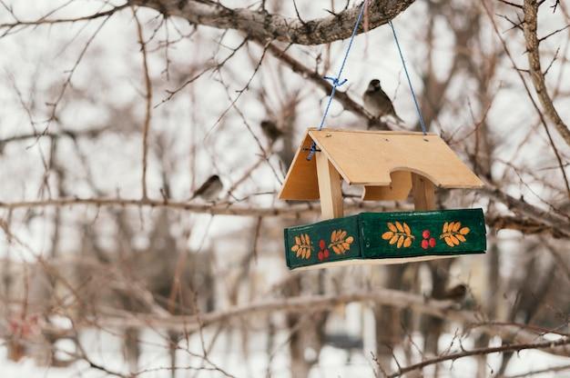 Vooraanzicht van vogelhuisje buiten in de winter aan de boom hangen Gratis Foto