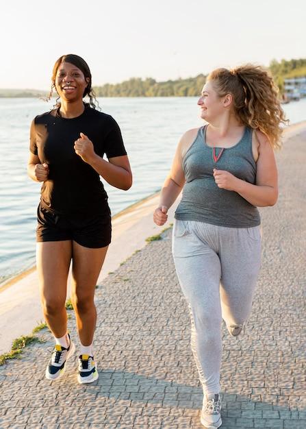 Vooraanzicht van vriendinnen joggen aan het meer Premium Foto