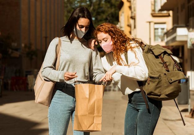 Vooraanzicht van vriendinnen met gezichtsmaskers buitenshuis met boodschappentas Gratis Foto
