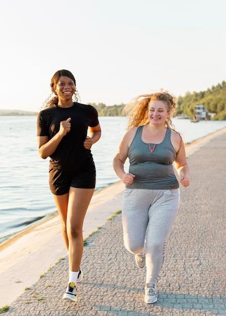 Vooraanzicht van vriendinnen samen joggen aan het meer Premium Foto