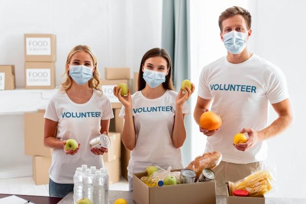 Vooraanzicht van vrijwilligers met voedsel voor donatie Gratis Foto
