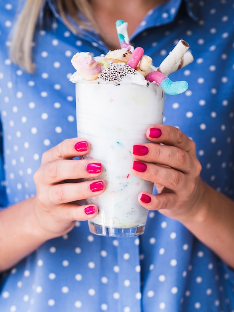 Vooraanzicht van vrouw die een milkshakeglas houdt Gratis Foto