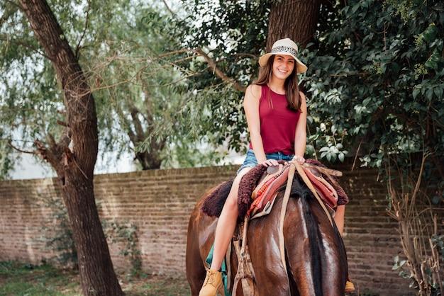 Vooraanzicht van vrouw die een paard berijdt Gratis Foto