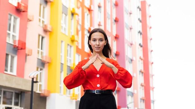 Vooraanzicht van vrouw die gebarentaal buitenshuis gebruikt Gratis Foto