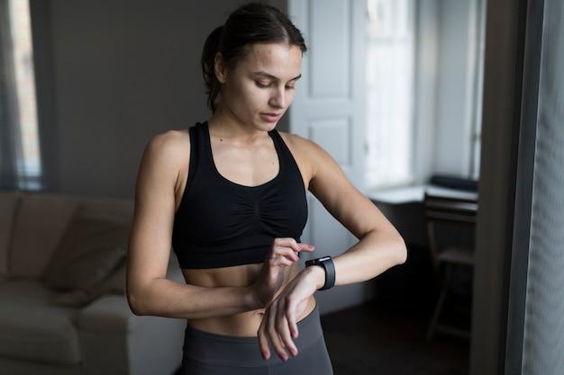 Vooraanzicht van vrouw die in athleisure haar smartwatch bekijkt Gratis Foto