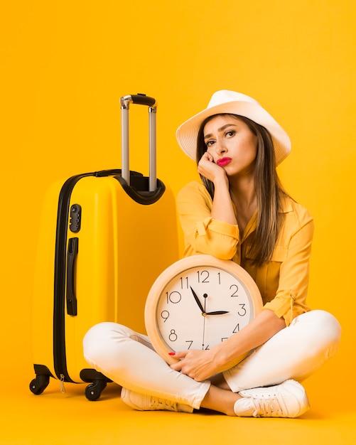 Vooraanzicht van vrouw die terwijl het houden van klok naast bagage stelt Gratis Foto