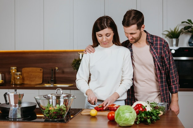 Vooraanzicht van vrouw en man die voedsel in de keuken bereiden Gratis Foto