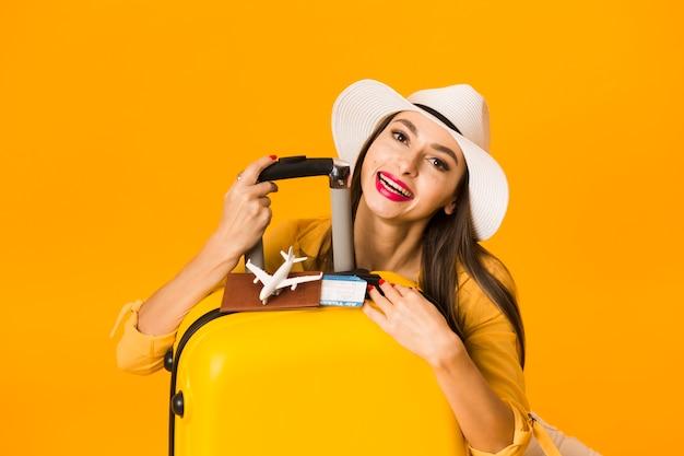 Vooraanzicht van vrouw het stellen met bagage en reisbenodigdheden Gratis Foto