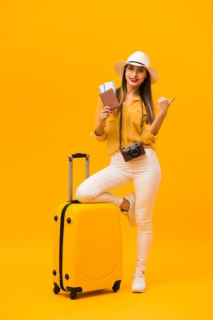 Vooraanzicht van vrouw klaar voor vakantie met bagage en reisbenodigdheden Gratis Foto