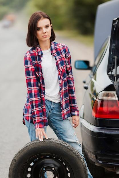 Vooraanzicht van vrouw met autoband Gratis Foto