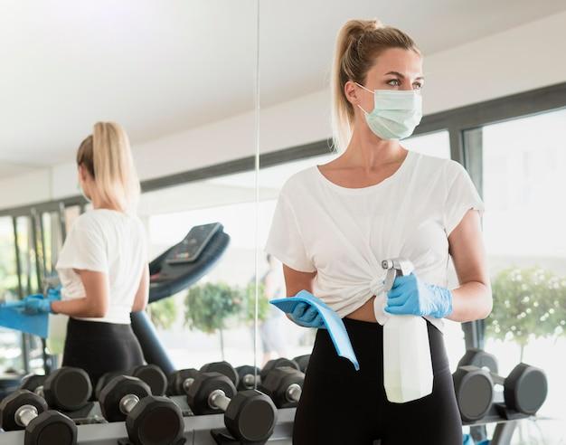 Vooraanzicht van vrouw met handschoenen en medisch masker dat gewichten desinfecteert in de sportschool Gratis Foto