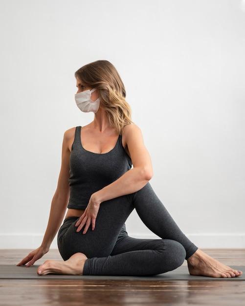 Vooraanzicht van vrouw met medisch masker die thuis yoga doet Gratis Foto