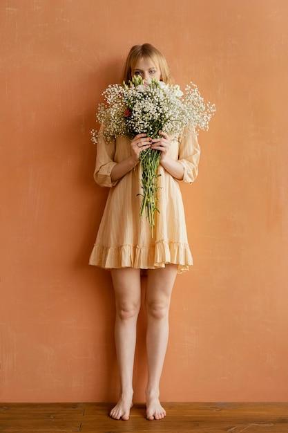 Vooraanzicht van vrouw poseren met boeket van lentebloemen Premium Foto