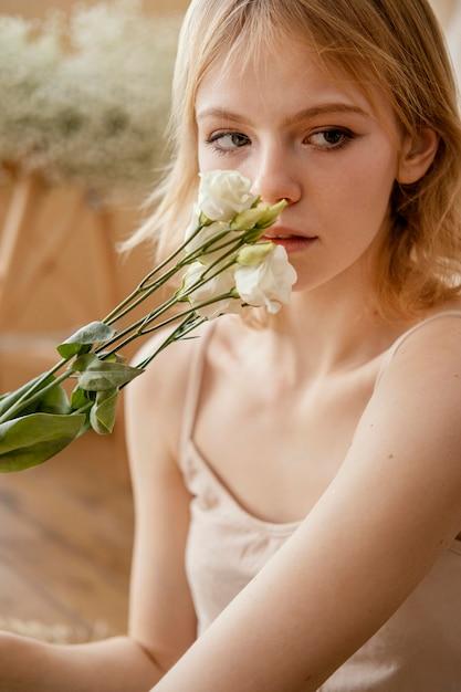 Vooraanzicht van vrouw poseren met delicate lentebloemen Premium Foto