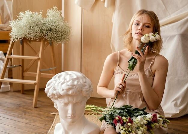 Vooraanzicht van vrouw poseren met lentebloemen Premium Foto