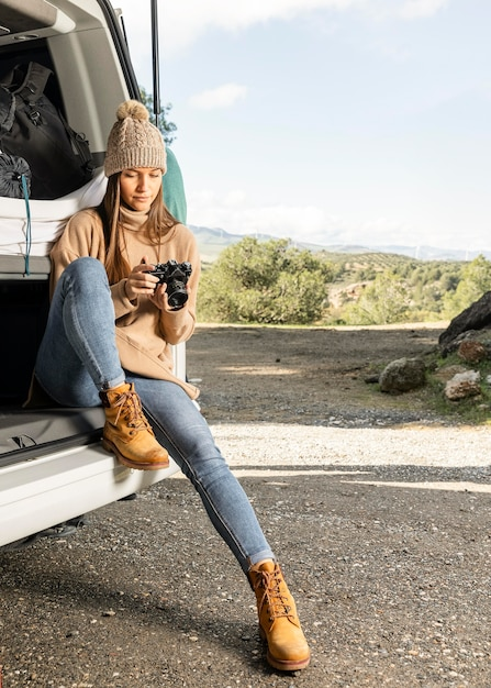 Vooraanzicht van vrouw zittend in de kofferbak van de auto terwijl op een road trip en camera vast te houden Premium Foto