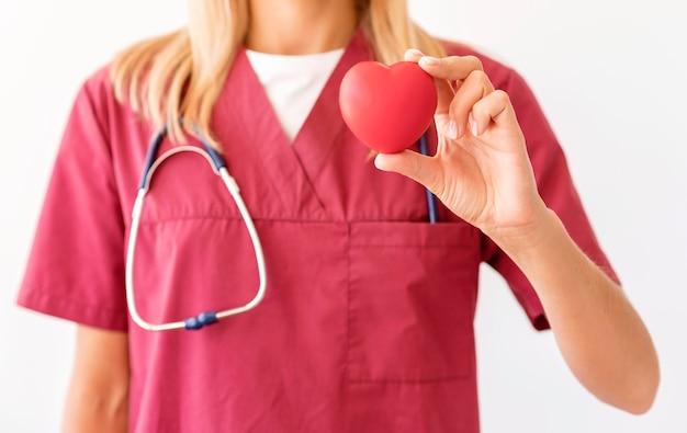 Vooraanzicht van vrouwelijke arts hartvorm houden Gratis Foto