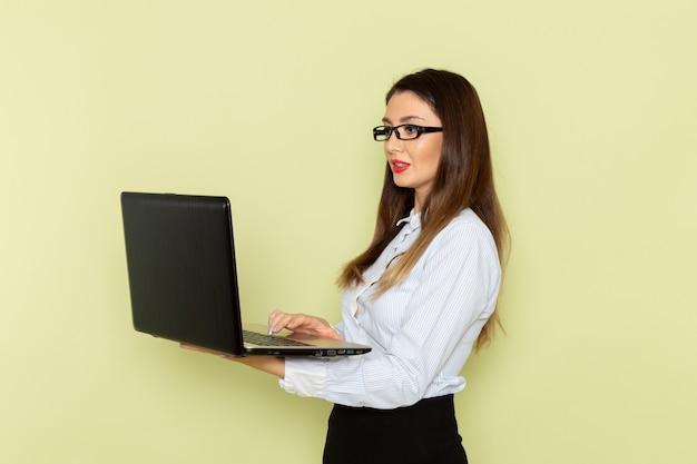 Vooraanzicht van vrouwelijke beambte in wit overhemd en zwarte rok die laptop op de lichtgroene muur houdt Gratis Foto