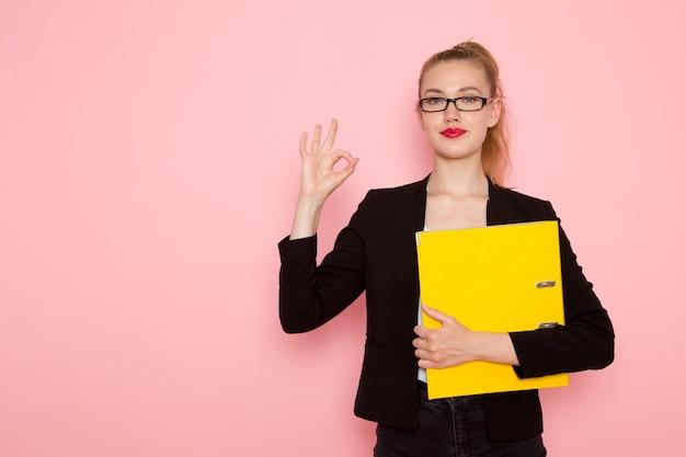 Vooraanzicht van vrouwelijke beambte in zwarte strikte jas met documenten op de lichtroze muur Gratis Foto